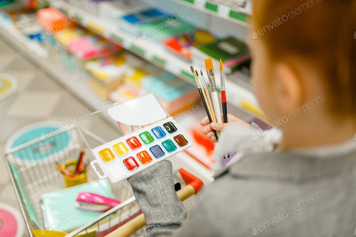 Schoolgirl choosing watercolor paints, stationery