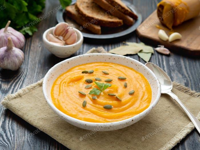pumpkin soup mashed in a white plate, pumpkin seeds, bread, garlic on dark wooden background