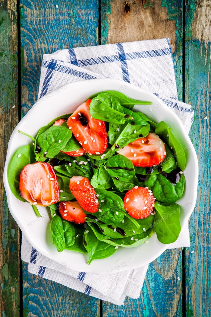 salad with fresh spinach and strawberries with balsamic sauce and sesame