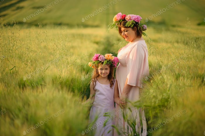 Mother and daughter in pink dresses in a green wheat field. On their heads they have floral wreaths