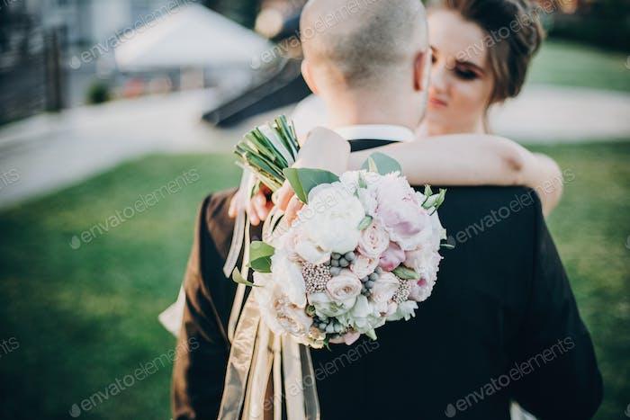 Portraits of beautiful tender wedding couple embracing in warm sunshine