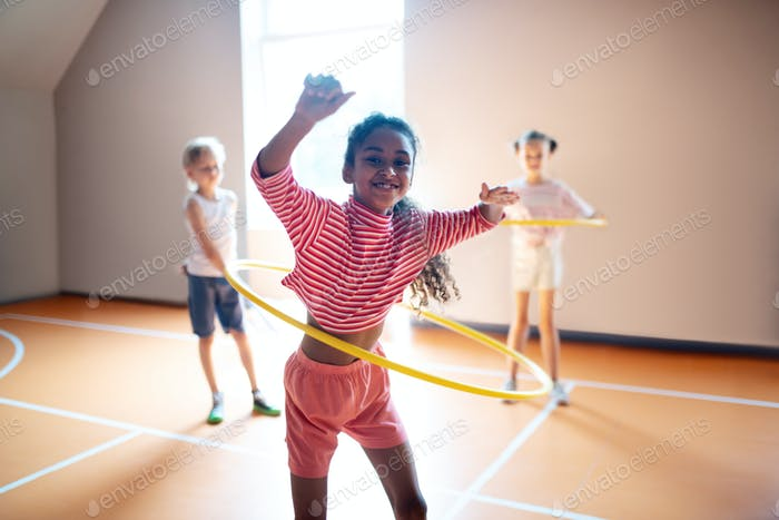 Cheerful curly girl enjoying active PE lesson