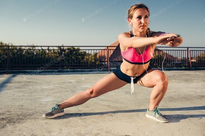 young sportswoman in earphones stretching on rooftop