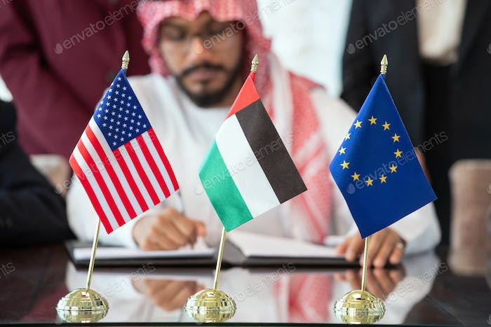 Flags of United States, European Union and United Arab Emirates on table