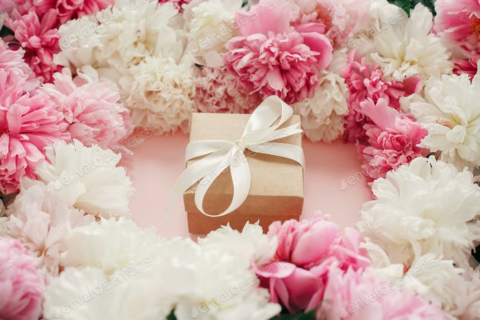 Pink and white peonies with gift box on pastel pink paper
