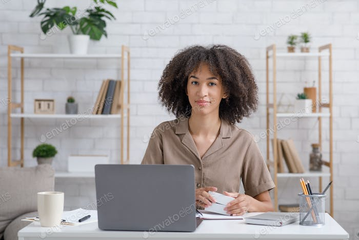 Alternative work at home. Cute african american woman with notepad looks at laptop