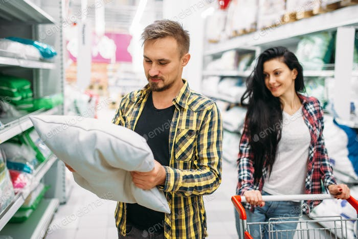 Happy couple buying pillow in supermarket