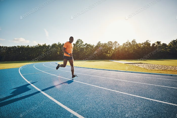 Fit young runner sprinting alone down a track