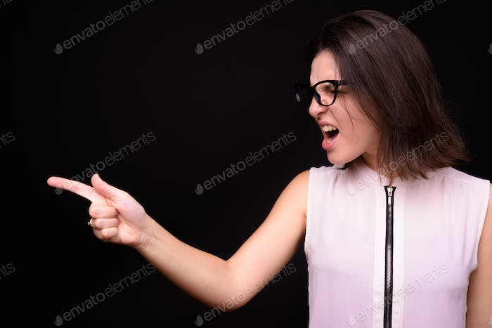 Young beautiful businesswoman against black background