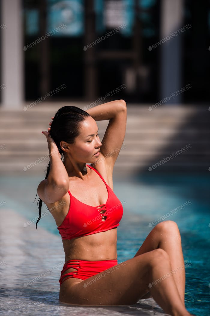 Portrait of beautiful, young lady in red bikini sitting poolside in luxury hotel