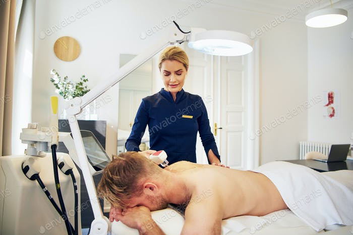Beautician performing an electrolysis hair removal procedure on a client