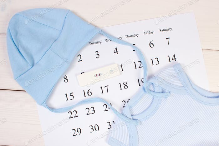 Pregnancy test with positive result and clothing for newborn on calendar, expecting for baby concept