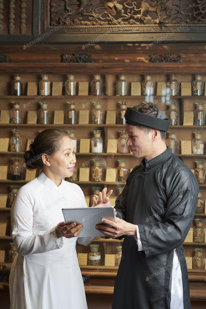 Pharmacist giving tasks to coworker