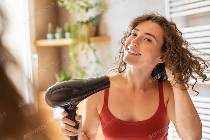 Mujer sonriente feliz usando secador de pelo en el baño