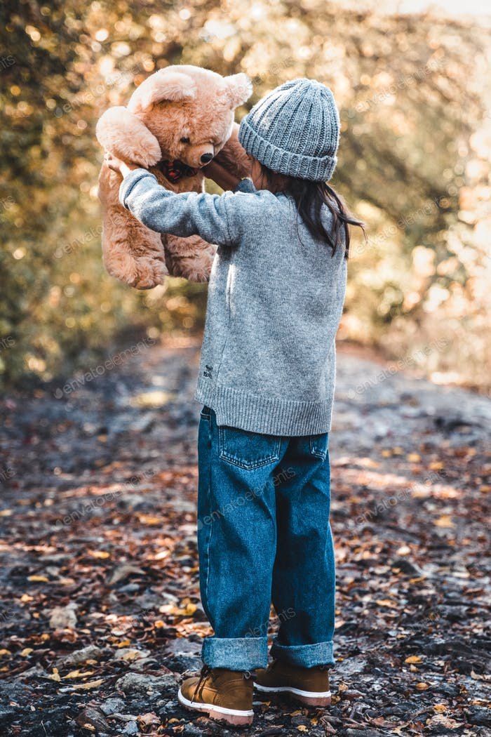 Little girl holds a bear in her arms on the background of nature on an autumn day