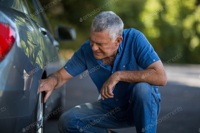Nan checking wheel of car on road