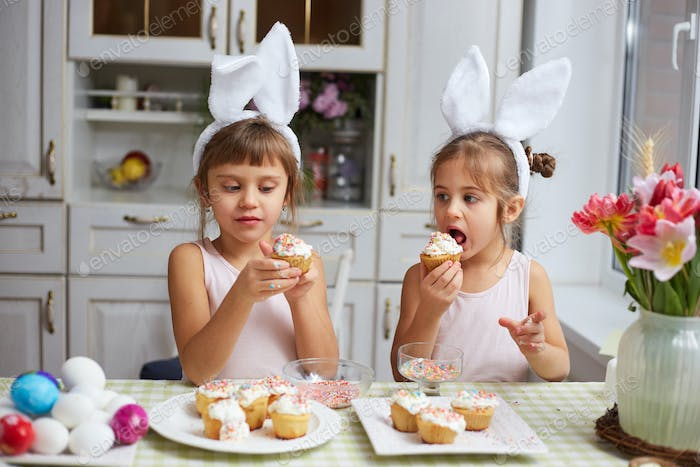 Two little sisters with white rabbit's ears on their heads eat small Easter cakes in the cozy