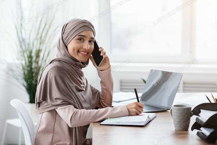 Arabic Female Secretary Talking On Cellphone And Taking Notes In Office