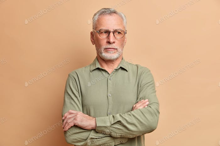 Mature bearded man executive keeps arms folded and stands thoughtful indoor thinks over future plans