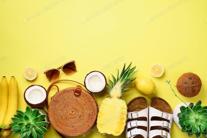 Stylish rattan bag, coconut, birkenstocks, succulent, sunglasses and yellow fruits on sunny