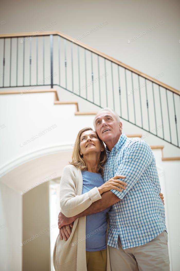 Seniorenpaar umarmen einander im Wohnzimmer