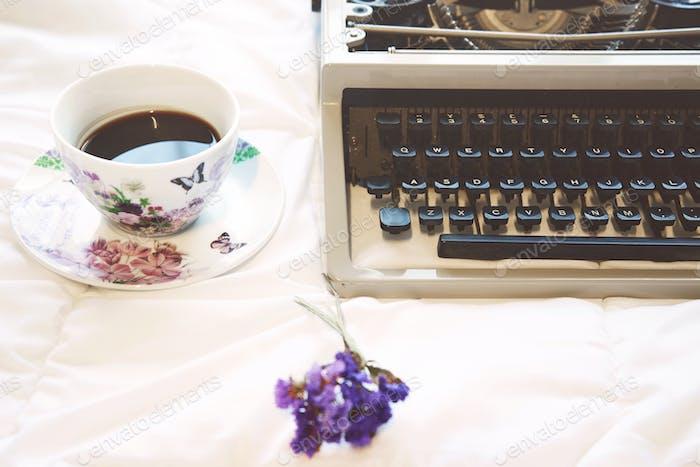 Máquina de escribir Vintage y taza de café en la cama