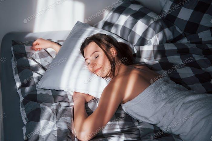 Weiches Kissen und süße Träume. Hübsche junge Frau liegt morgens auf dem Bett in ihrem Zimmer