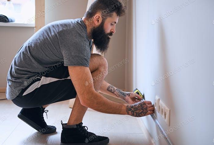 Carpenter measuring a wall.