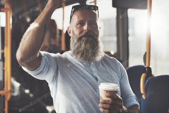 Mature man drinking coffee while standing on a bus