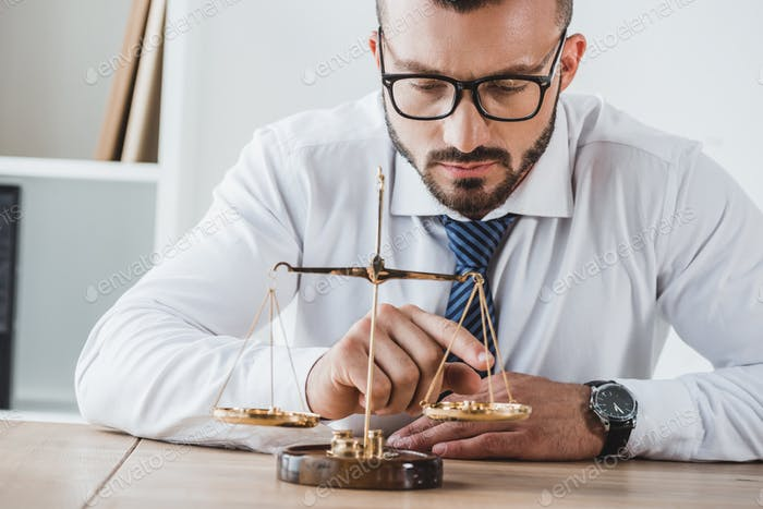 business adviser touching scales with coins in office