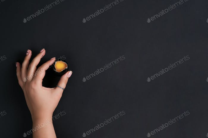 Creative backdrop with woman's hand hold Easter painted black egg broken with yellow yolk on the