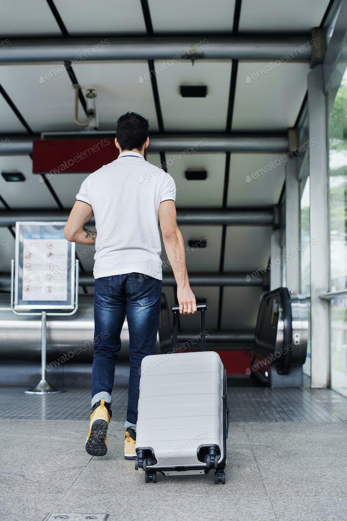 White man carrying luggage