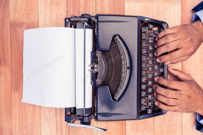 Businessman typing on typewriter at desk in office