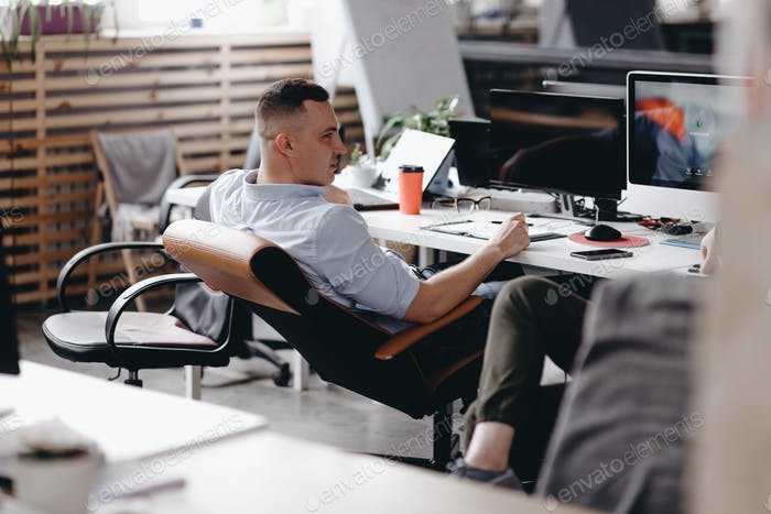 The guy dressed in office style clothes is sitting in an office chair at desk with laptopo in the