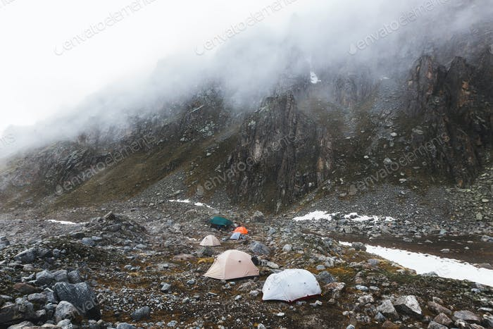 Сamping with tents high in the mountains in winter. Fog, snow and cold weather.