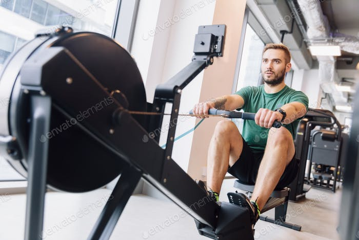 Active athlete man doing rowing workout