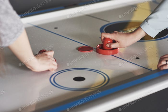 Hands of young people holding striker on air hockey table in game room