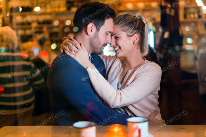 Happy couple hugging at bar and having date