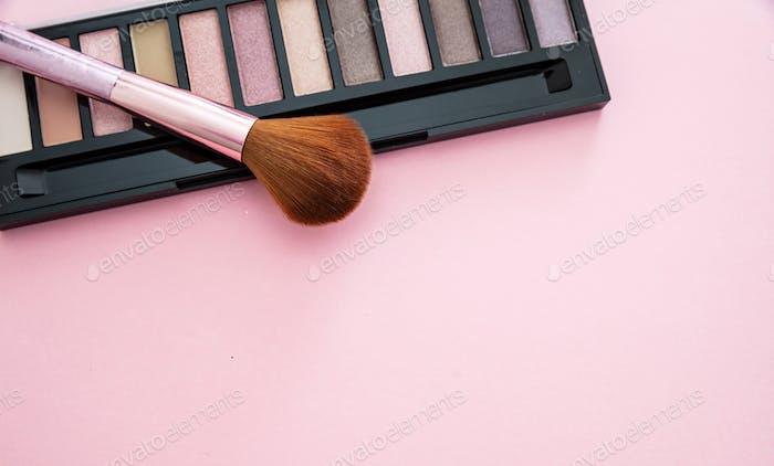 Eyeshadow pallete kit against pink background, copy space