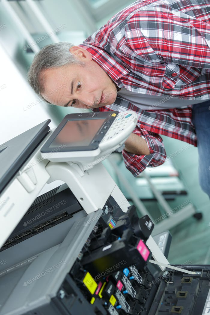 Man bending down to photocopier