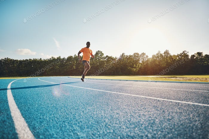 Focused young runner sprinting alone down an outdoor track