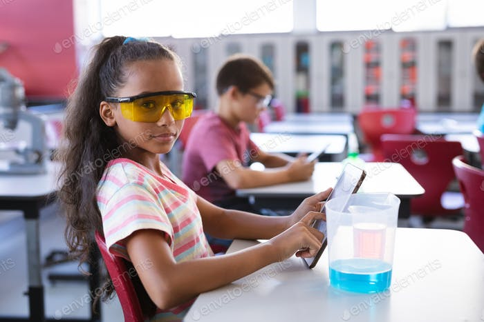 Porträt eines afroamerikanischen Mädchens mit digitalem Tablet im Wissenschaftsunterricht im Labor