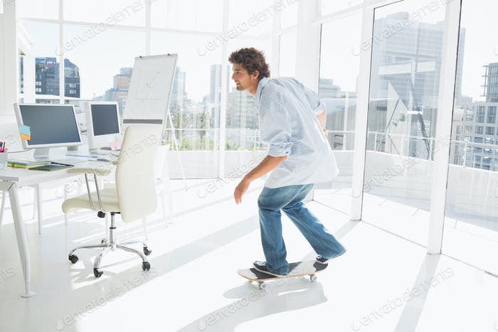 Full length of a happy young man skateboarding in a bright office