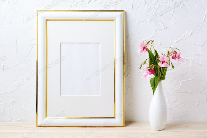 Gold decorated frame mockup with flower bouquet in elegant vase