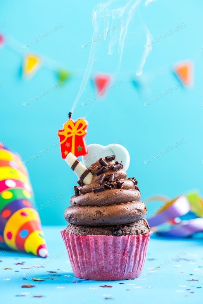 Bunte Cupcake mit einzelner Kerze ausblasen