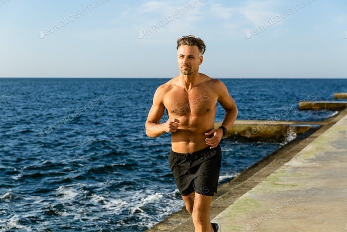 fit adult shirtless man jogging on seashore