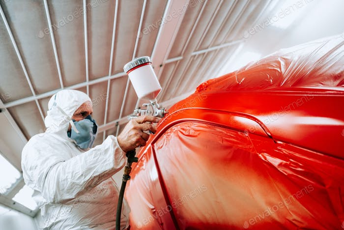 automotive industry mechanic engineer using spray gun and painting a red car