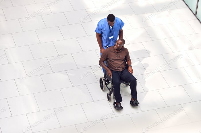 Overhead View Of Male Nurse Wheeling Patient In Wheelchair Through Lobby Of Modern Hospital Building