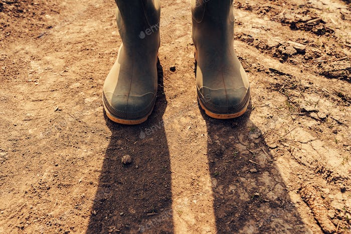 Farmer standing on dirt country road, close up of boots