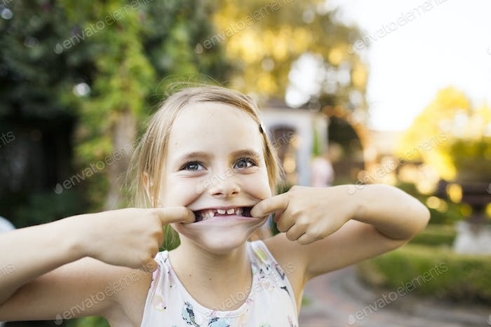 Portrait of girl pulling faces in garden